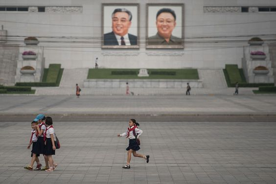 In a photo taken on July 9, 2016 a child runs before the portraits of former North Korean leaders Kim Il-Sung (L) and Kim Jong-Il (R), in Pyongyang
