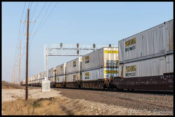 J. B. Hunt containers pass under the signal bridge at Edgerton, KS. as they take a ride on an eastbound BNSF stack train.