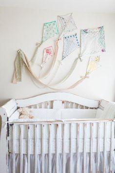 Des cerfs volants en tissu et rubans au-dessus du lit de bébé