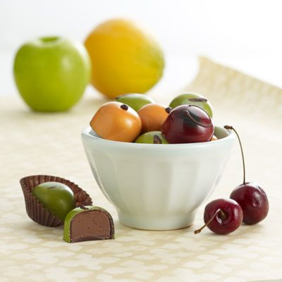 "John & Kira's Chocolates - whipping up some darling new treats for the coming fall season that I can't wait to try - ""apples"" filled with apple cider cinnamon and cardamom ganache, tart red ""cherries"" with dark chocolate and brandy ganache, and white chocolate ganache ""oranges."""
