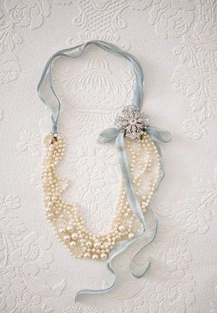 Fold beads in half, tie ribbon, add charms and flower to hide fold. Seems easy enough. love the ribbon color