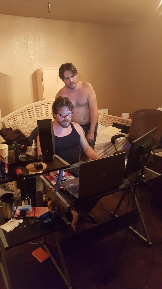 Photo of me and my identical twin brother looking at a computer on a desk in a normal bedroom. We're both Caucasian, physically fit, blonde hair, blue-eyed, wear glasses and have short-length bears