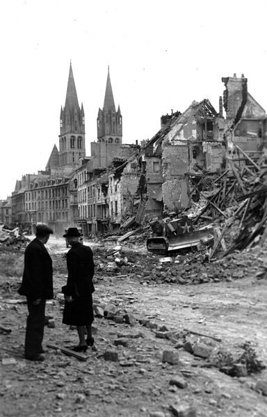 2 civilians looking at a Canadian bulldozer in Rue de Bayeux in the city of Caen, in the background, the 2 towers of the Abbaye aux Hommes - 10 July 1944.  Approximately 35,000 citizens of Caen were rendered homeless after Allied bombing.