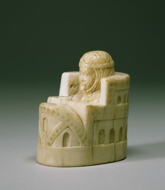 Chess Piece of a Queen: This chess piece of a queen seated inside a castle is modeled on similar pieces made in the Arab world in the 8th and 9th centuries & brought to western Europe as gifts or articles of trade. The queen's headdress, a close-fitting hood with headband, is typical, though, of royal garments worn in 12th-century Spain. The piece is carved from a walrus tusk, used as a cheaper alternative to elephant ivory.