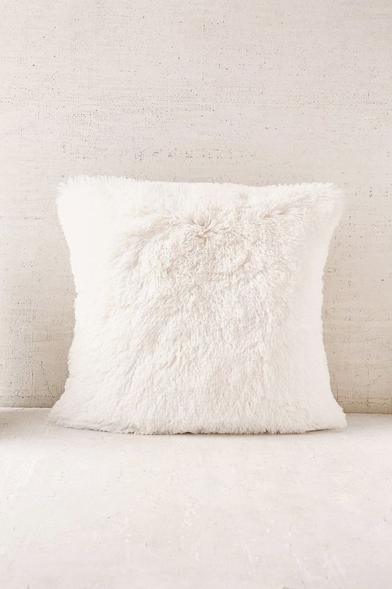 Who wouldn't want to cuddle with this Urban Outfitters Plum & Bow Faux Fur Pillow?