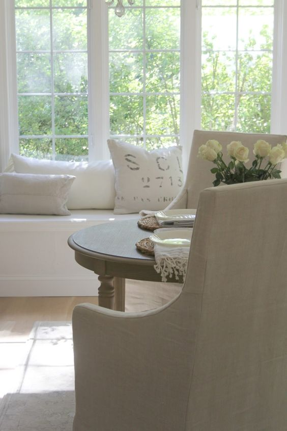 French Country kitchen decor in a serene white European inspired home. Window seat with linen pillows, Belgian linen slipcovered arm chairs, and a round farm table. Design by Hello Lovely Studio. #farmhousekitchen #windowseat #frenchcountry #frenchfarmhouse #kitchendecor #kitchendesign #breakfastroom #belgianlinen #interiordesign