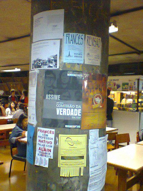 FAU - Papel colado sobre coluna. Propagandas de inciativa privada. Visa frequentadores da cantina.