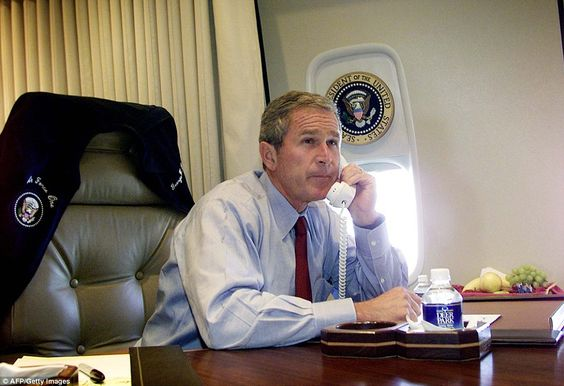 President George W. Bush talks on the phone with New York Mayor Rudy Guiliani and Gov. George Pataki aboard Air Force One in the wake of the attacks on September 11