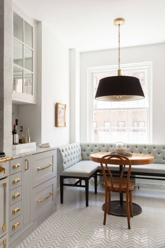 Classic kitchen design with grey cabinets, #brasshardware, tufted #banquette, Bentwood chair, and round bistro table - on Hello Lovely Studio