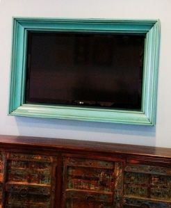 A Custom Teal TV Frame helps the tv blend in with your decor