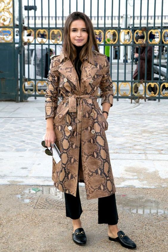 Miroslava Duma in a python trench coat over a black turtleneck and cropped flare trousers with Gucci slip-on loafers