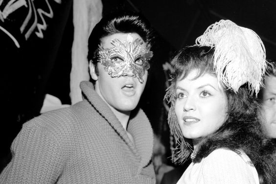 Elvis Presley wears a mask as he and actress Joan Bradshaw celebrate Halloween at a party in Hollywood, Calif., in 1957.