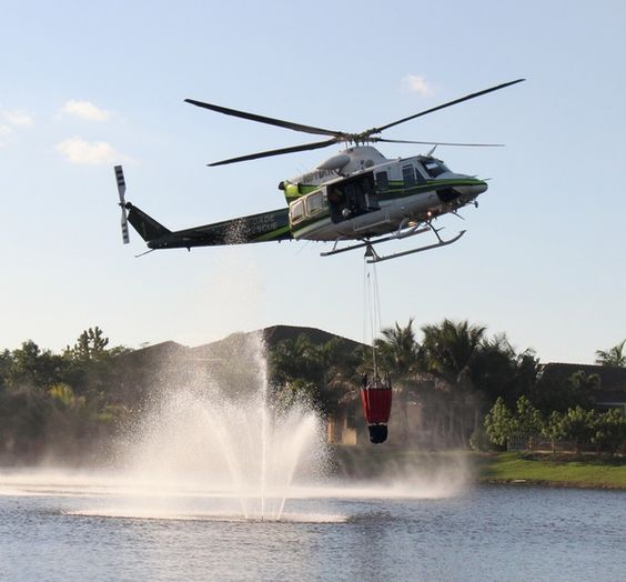 Air Rescue fills its water bucket to do a water dump on a brush fire in Kendall on March 5th. Photo by Edward Figueroa
