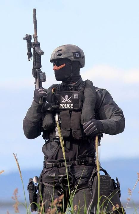 A Royal Canadian Mounted Police (RCMP) Emergency Response Team (ERT) operator in tactical gear with a Colt C8 assault carbine during a public exhibition.