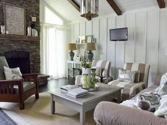 Board-and-batten walls, tongue-and-groove ceiling, old wooden beams and stacked stone fireplace with reclaimed wood as the mantel make this the perfect backdrop for a cottage living room... the focal point is the fireplace and the furniture layout is for conversation. Photography by Jennifer Kesler