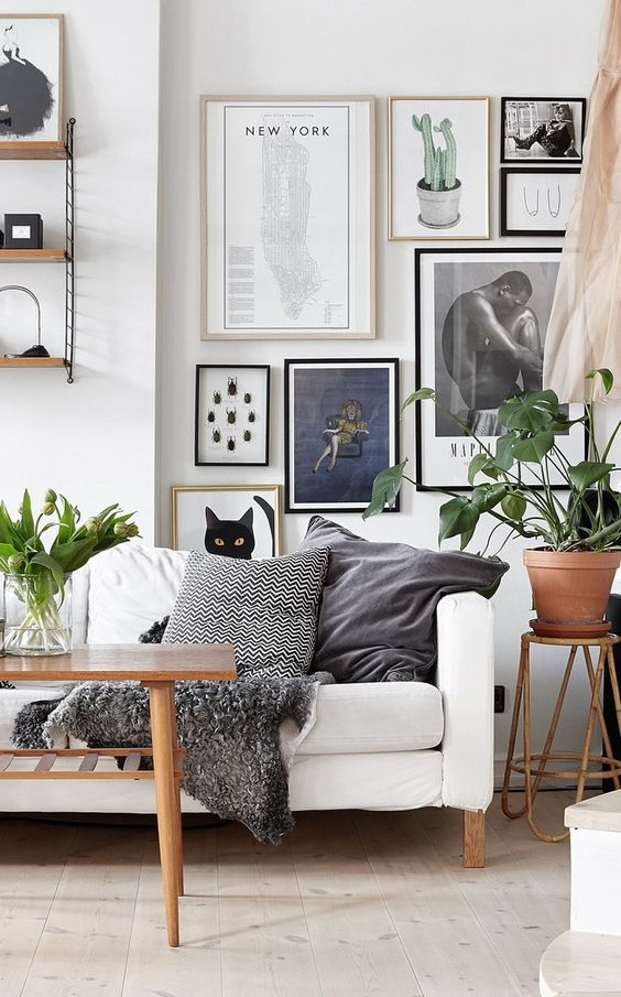 Bright living room with light wood, white sofa, plants, and neutral gallery wall: