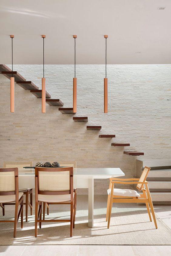 Sala de jantar moderna com mesa em laca branca, cadeiras em estilos diferentes, pendentes em cobre e parede texturizada com pedras naturais