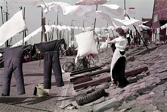 Huisvrouw hangt de was te drogen aan een waslijn op de dijk te Volendam, circa 1955.  Washing-day in Volendam, the Netherlands, about 1955.