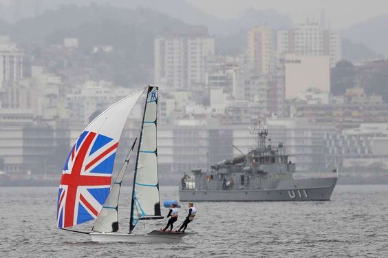 Brazilian sailors looking to shine on polluted Guanabara Bay - August 7, 2016 - Sailors Charlotte Dobson and Sophie Ainsworth of Great Britain sail past a Brazilian navy ship in their 49erFX sailboat during a sailing training session of the 2016 Summer Olympics in Rio de Janeiro, Brazil, Sunday, Aug. 7, 2016. (AP Photo/Gregory Bull)