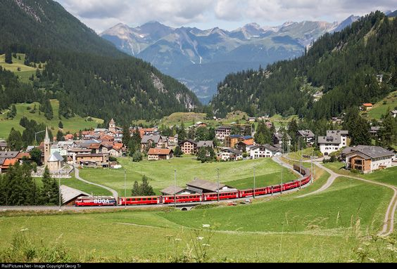 Ge 4/4 III # 646 of the RhB with publicity paint scheme for BÜGA, Grisons public transport ticket, is pulling Regio Express 1129 from Chur to St.Moritz over the Albula line, on the lowest level of the loops above Bergün.