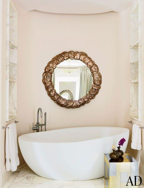 An 18th-century mirror is mounted above the Waterworks tub in a serene master bath.