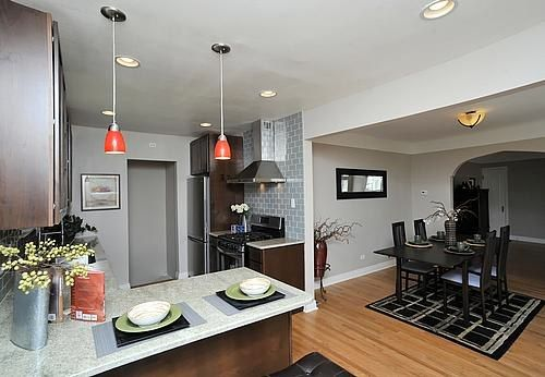Here's an amazing #kitchendesign from a customer who installed a #cavaliere #rangehood in their kitchen. This #design has lots of color spread throughout that pops. The red kitchen lighting stands out and the gray #backsplash matches the gray place mats and the vase. The dining room looks fantastic as well. What a difference!