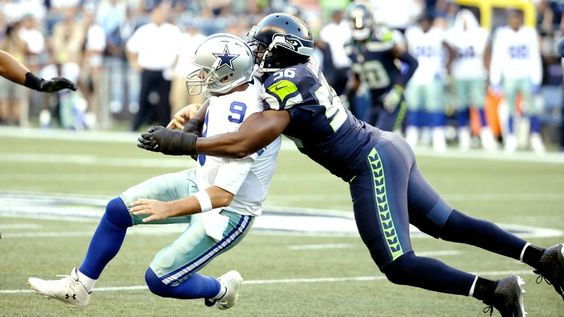 Seahawks' Cliff Avril checks on Tony Romo after hit injured Cowboys QB