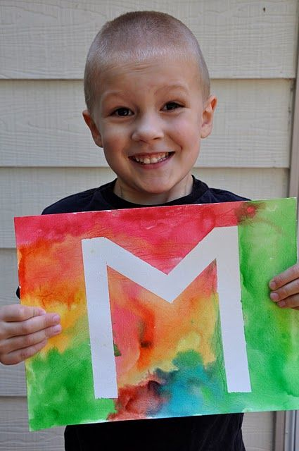 Painters tape for the letter...remove later.  And just put watercolors all over the paper or canvas.  Riley would enjoy this!