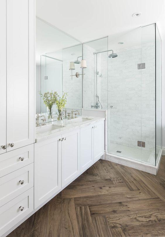 Master bathroom with herringbone wood floor, marble shower and countertops, white cabinets, double vanity   Ali Budd Interiors