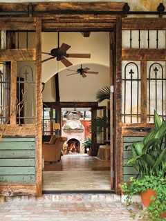 Salvaged wood and wrought iron create the unique sliding doors that open onto this porch. Antique bricks complement the weathered wood of the doors.