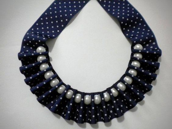 Collar babero con perlas y cinta azul marino de lunares blancos.
