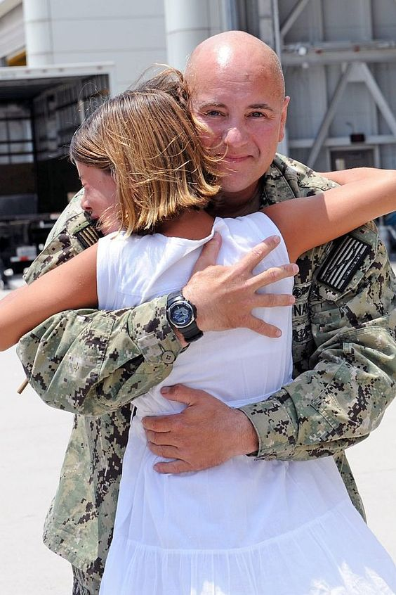 Chief Warrant Officer 5 Hatler Riddle, assigned to Fleet Logistics Squadron (VRC) 40, reunites with his daughter during a homecoming celebration at Naval Station Norfolk after an 8-month deployment.