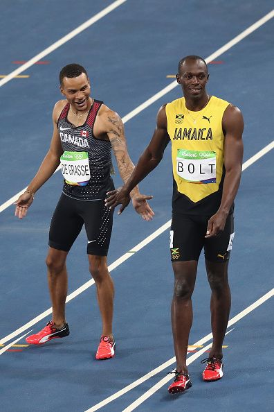 Usain Bolt of Jamaica and Andre De Grasse of Canada react after the Men's 100…