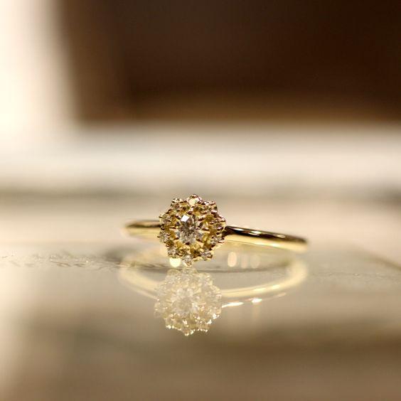 0.1カラットのまわりを直径1㎜のダイヤモンドが取り巻くエンゲージリング。 地金はゴールド。リングアームは、丸く繊細にお仕立てしました。  [engagement,wedding,ring,婚約指輪,ウエディング,]