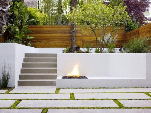 The lines of green moss in the floor balances all the slick concrete and gray stone of this modern patio.