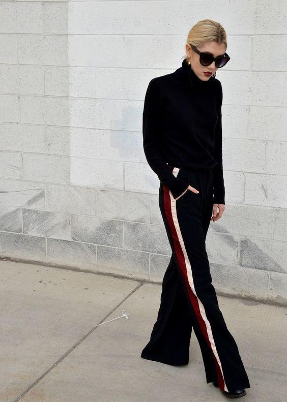 10 looks super estilosos com calça esportiva. Suéter preto com gola alta, calça preta com listras nas laterais, sandália de salto, track pants, look all balck, todo preot