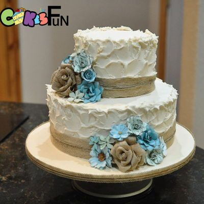 """Rustic Wedding Cake  Two tiers (10"""" and 6"""" double layers) with ivory buttercream. Cake bordered with brown burlap, twine and turquoise flowers. The..."""