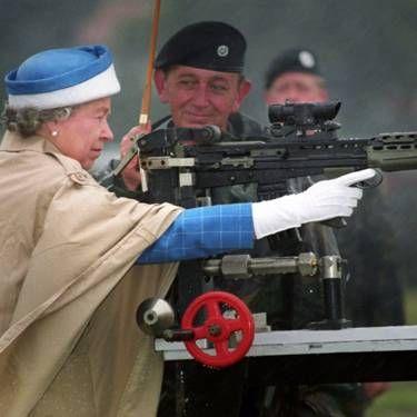 Королева Елизавета II под руководством инструктора стреляет из автомата SA80.