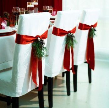 Christmas décor: a red ribbon, a pine cone, and a sprig from a pine tree on dinning room chairs