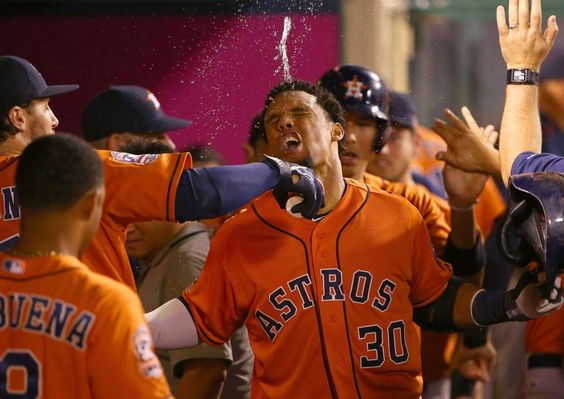 Cool hit -  Carlos Gomez of the Houston Astros celebrates in the dugout as he is doused with water he hit a two-run home run against the Los Angeles Angels Sept. 11 in Anaheim, Calif. The Angels won 3-2. -  © Victor Decolongon/Getty Images