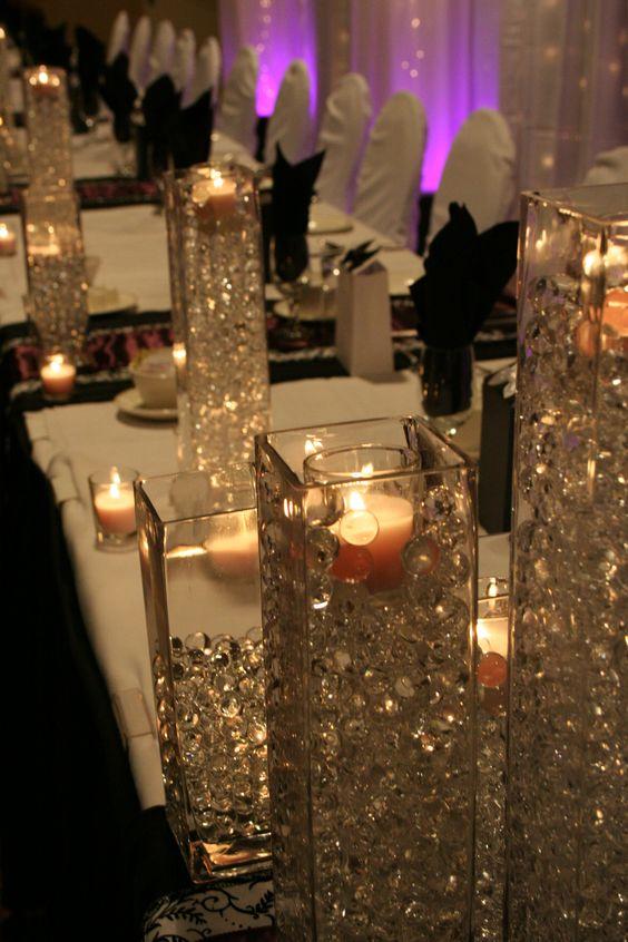 Jarrones altos con cuentas y velas sirven como centros de for Decoracion de jarrones