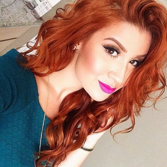 A lovely redhead with long curly haircut, Side part. Purple lips.