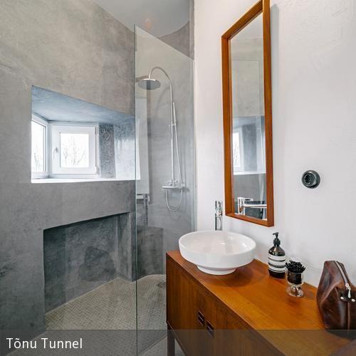 Das Bad im alten Holzhaus wurde neu renoviert. Dabei wurde es schlicht und dezent gehalten, mit Betonoptik und Holzelementen. - DIE GANZE GESCHICHTE AUF ROOMIDO.COM