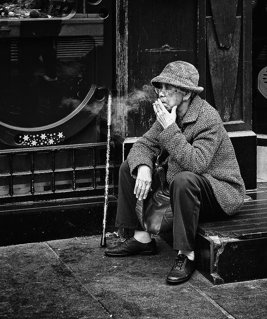 An elderly #Chinese lady sits on the steps of the Play 2 Win amusement arcade on Gerrard St, Chinatown, #smoking a cigarette