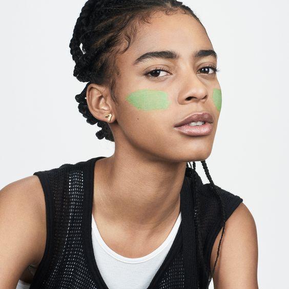 Una chica de piel morena con el pelo recogido en trenzas y dos pegotes de mascarilla verde en los pómulos. Un medio plano donde se aprecia un chaleco negro sin mangas sobre una camiseta blanca de tirantes