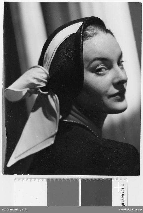 Av Maud Roser. Porträtt av modell i hatt med ljust dekorband. Fotograf: Erik Holmén, ca 1950-1955
