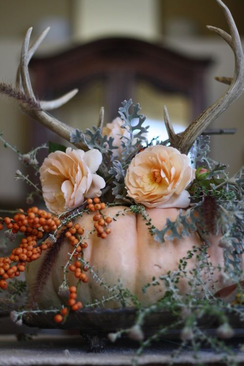 Stunning Thanksgiving Centerpiece Idea || Antlers, flowers, berries, and greenery tucked into the center of a hollowed out pumpkin.