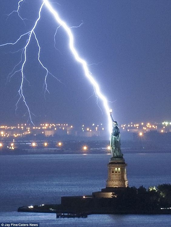 Bolt from the blue: Jay Fine captured this incredible image as lightning strikes the Statue of Liberty in New York harbour: