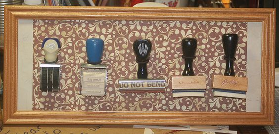 I covered the backing board with scrapbooking paper.  Then I punched holes and threaded hair ties through the holes to make loops for the stamp handles.  I think it turned out nice.  stamp storage and display by Kerri's memories, via Flickr