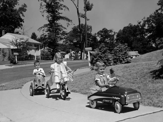 Boy And Two Girls On Suburban Sidewalk Riding Tricycle And Toy